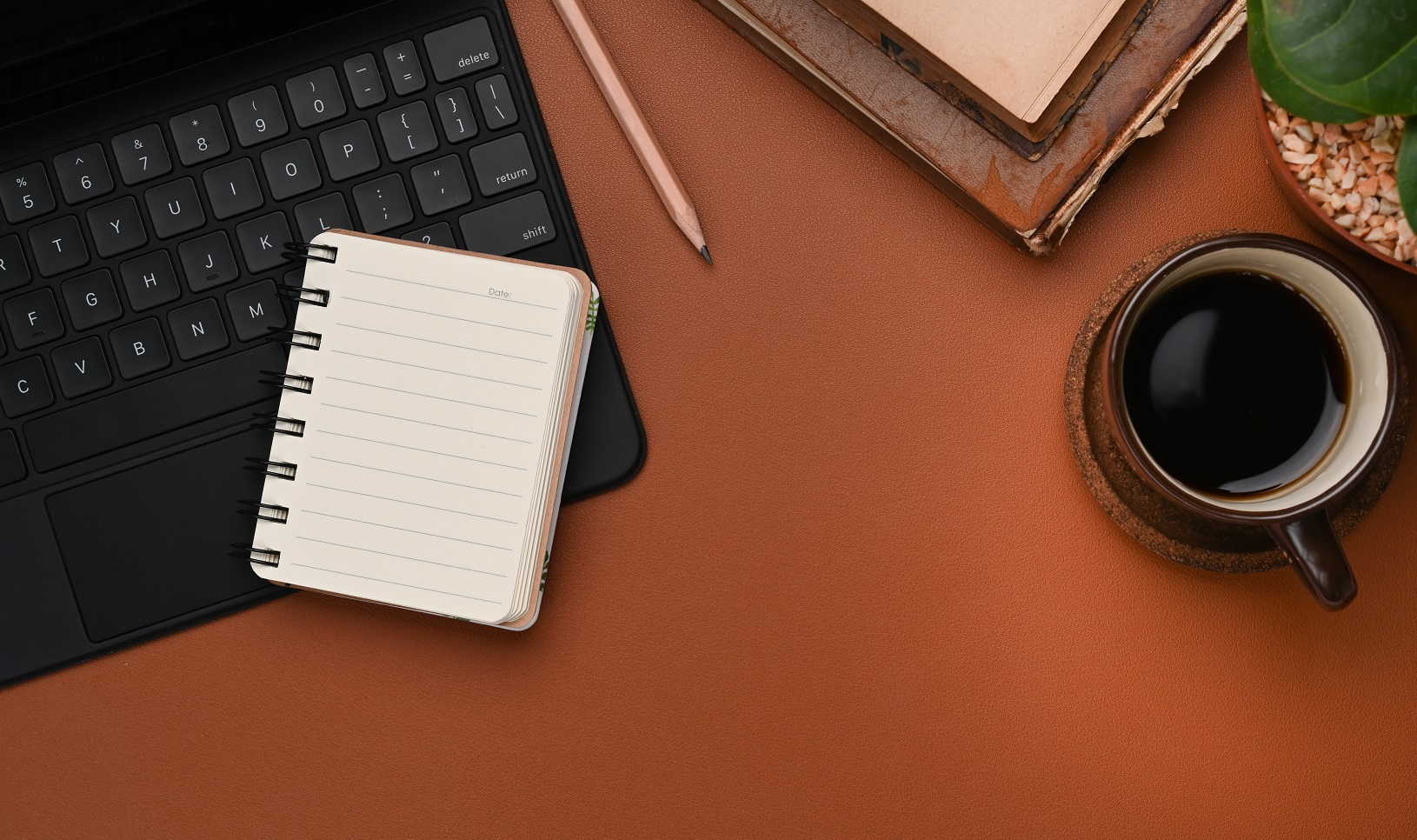 Overhead shot of contemporary workplace with coffee cup, notebook, keyboard and copy space brown leather.