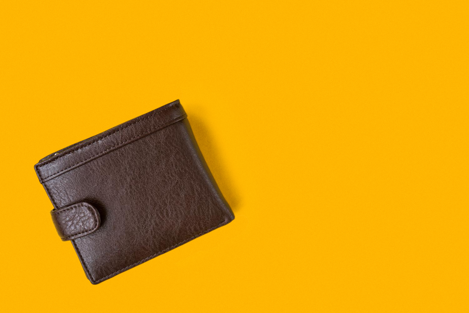 Lone brown wallet on a yellow background