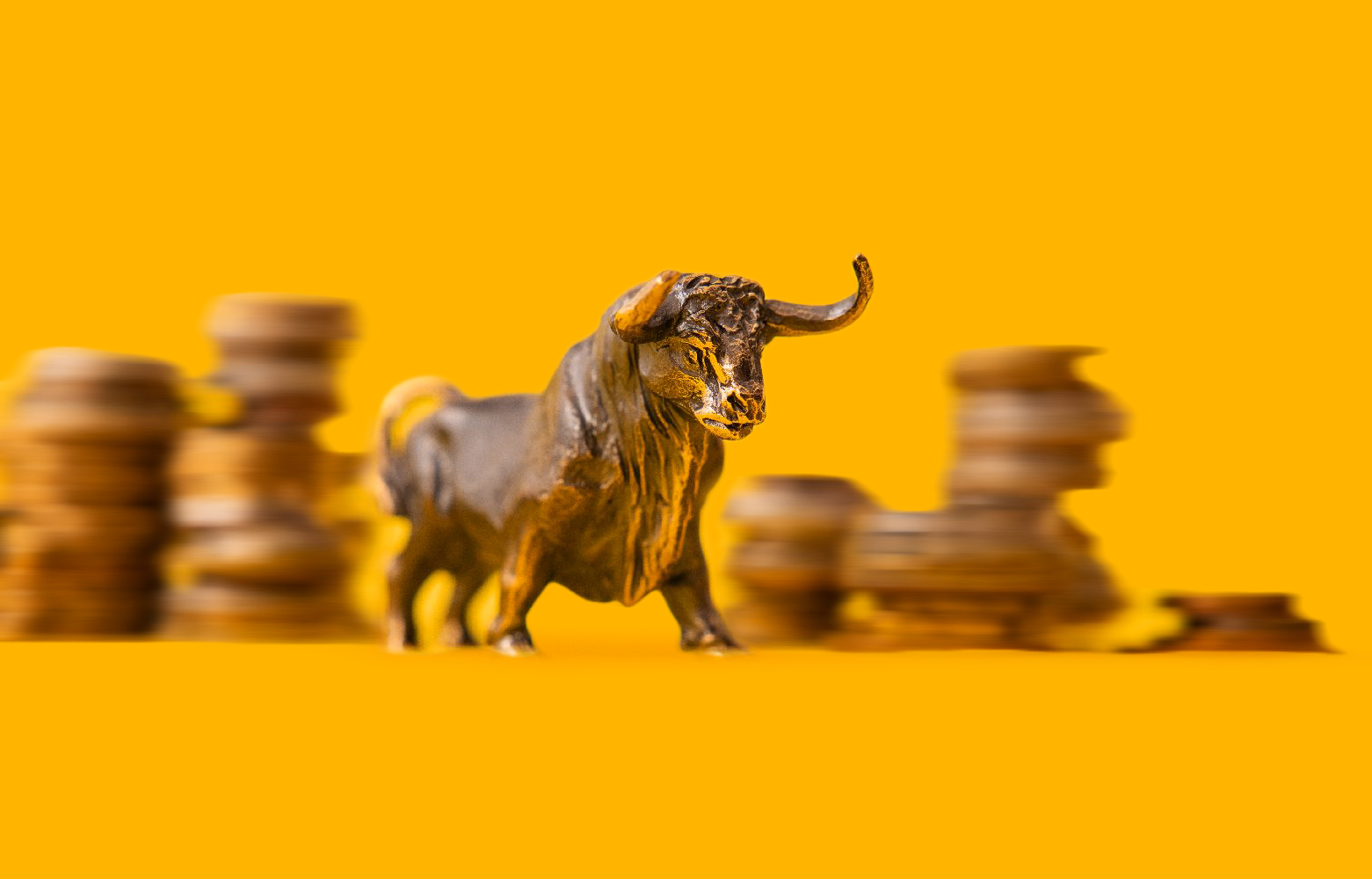 A bull figurine in front of stacked coins on a yellow background