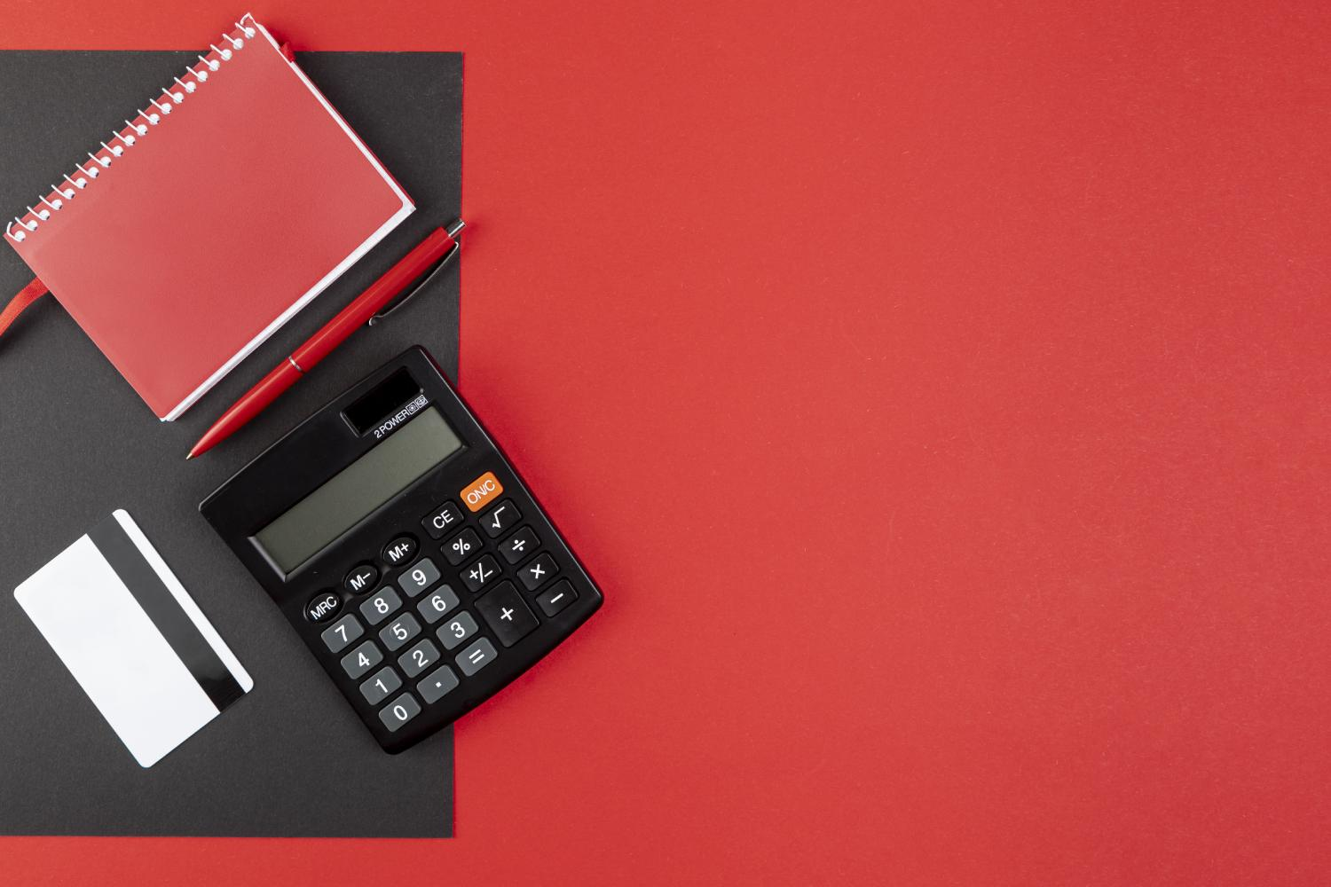 Calculator, credit card, and a writing pad on red background