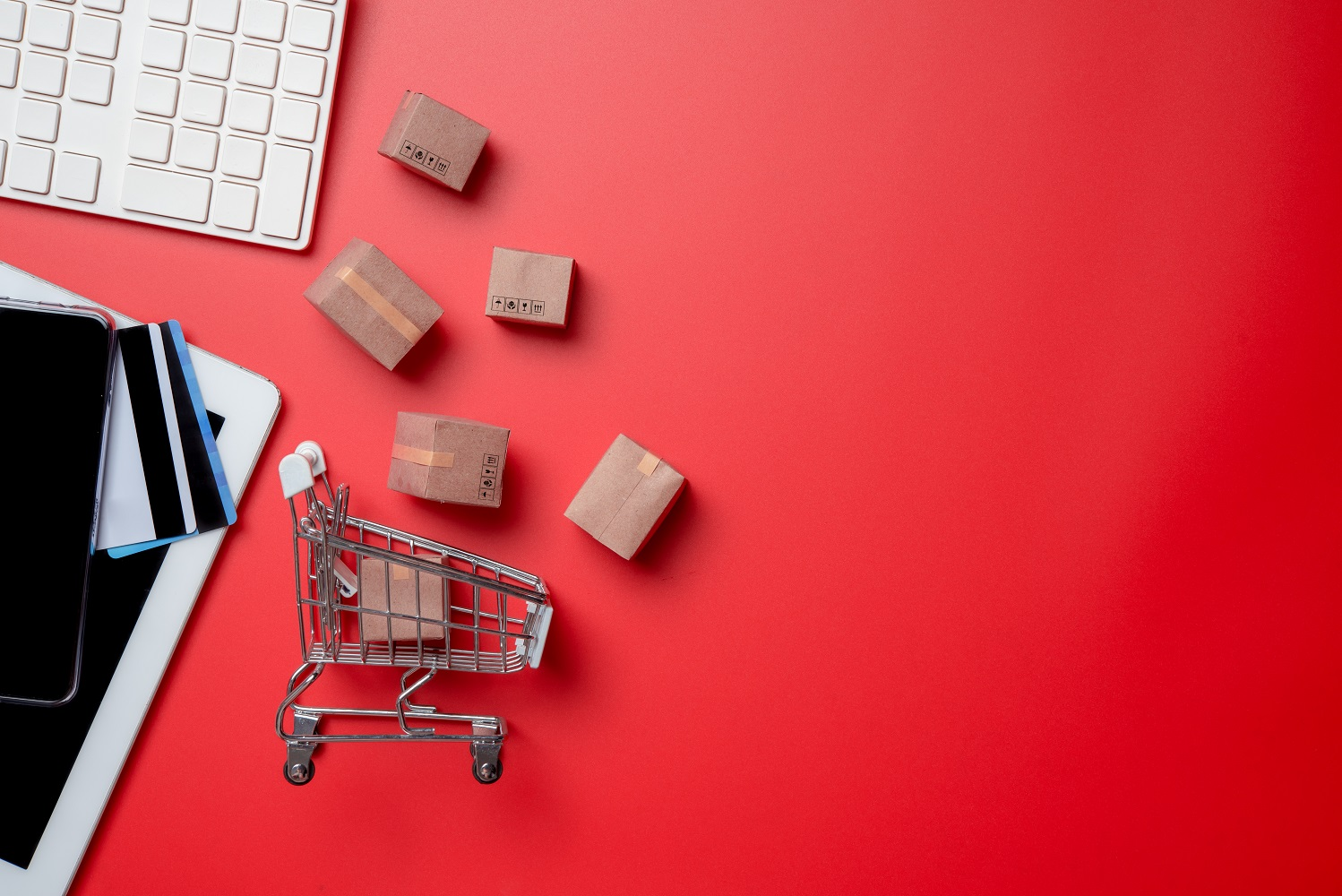 Online shopping, scatered office equpment and a miniature shopping cart