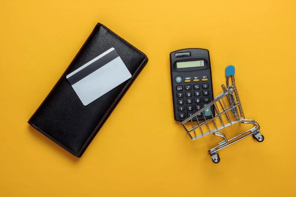 A calculator, wallet, credit card, and micro shopping trolley on a dark yellow background